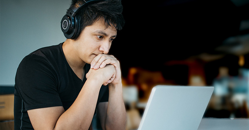 Young man looking at laptop with headphones