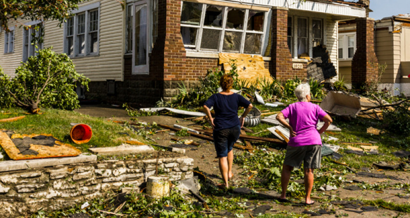 Two women standing on the front lawn of a house damaged by natural disaster.