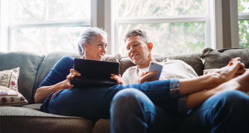 Couple on couch looking at a laptop