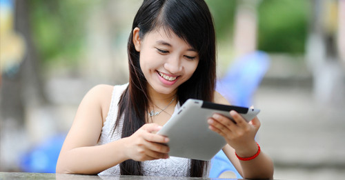 Young lady smiling at tablet