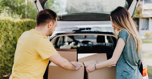 A man and woman packing boxes into a car