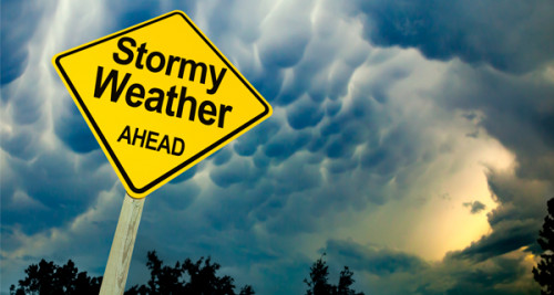 Outdoor sign with the words Stormy weather ahead written on it